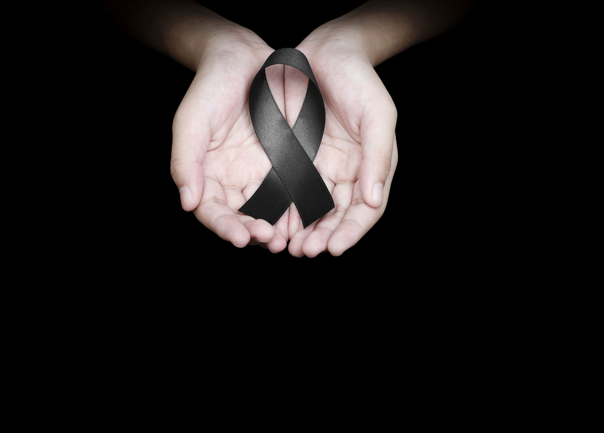 Quelle: Hand holding black ribbon on black background mourning awareness sign © Love the wind | Fotolia.com