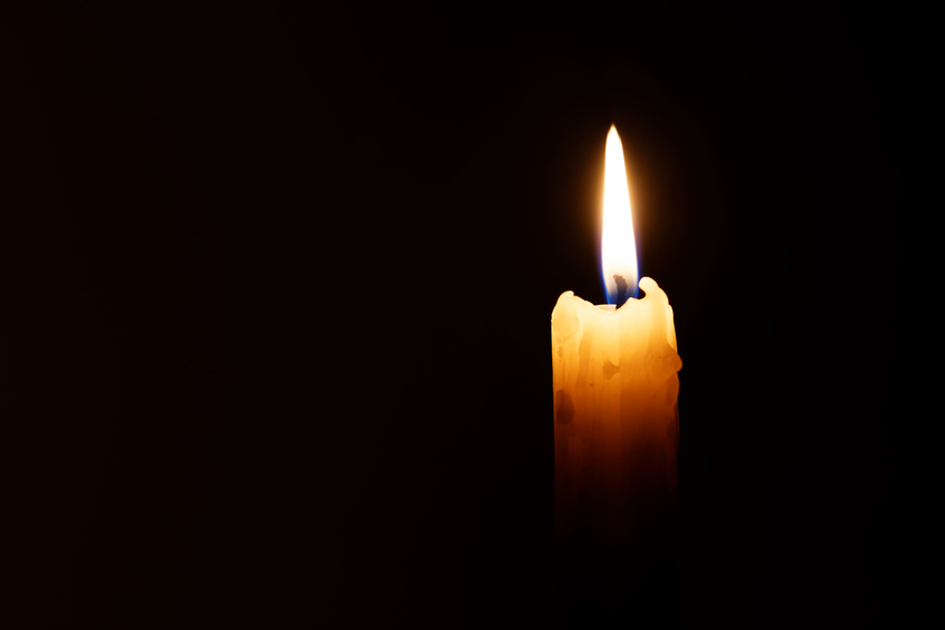 The candle's image is isolated against a black background and fades into a shadow.