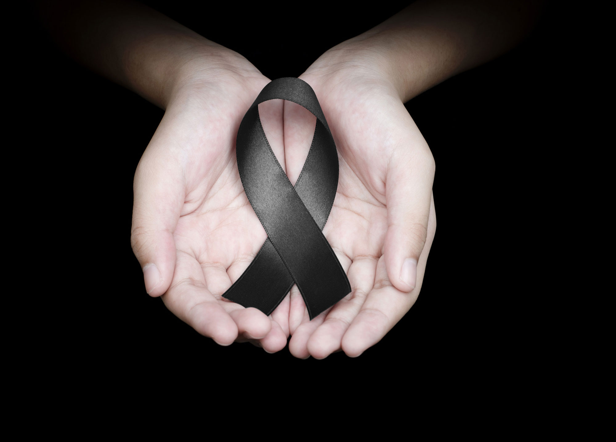 Quelle: #160526015 Hand holding black ribbon on black background mourning awareness sign © Love the wind | fotolia.com